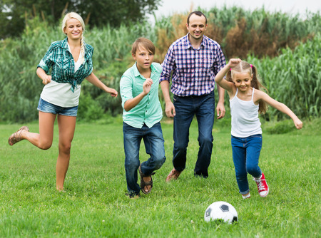 kids outside: Cheerful positive children and parents running with ball at sunny day