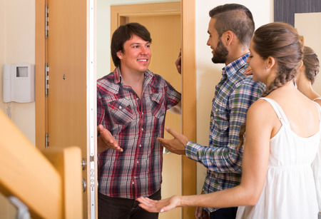 invitando: young family couple inviting friend in the apartment