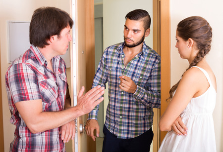 neighbour: Family couple having conflict with angry male neighbour at the door Stock Photo