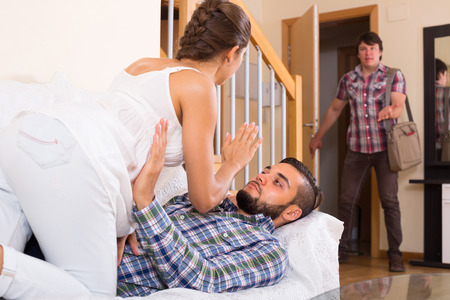 Surprised young husband discovering his cheating wife at home