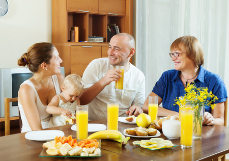 three generations: happy ordinary three generations family over table with friuts with juice at home interior