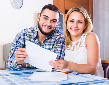 middle joint: Young smiling couple filling forms for joint banking account at the table