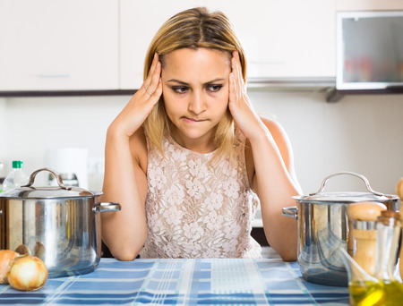 dispirited: Tired adult russian  woman leaning her elbows at the kitchen Stock Photo