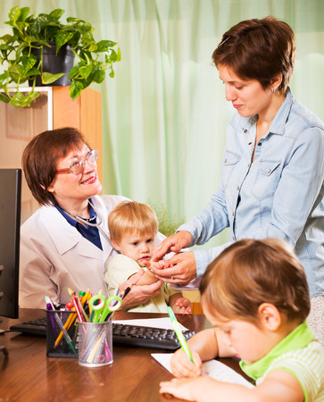 general pediatrician: mother with two children at a reception at the pediatrician at the clinic