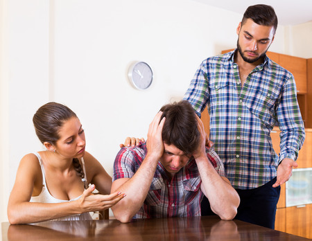 lovers quarrel: Portrait of attractive girl and two guys at home: problems of love triangle