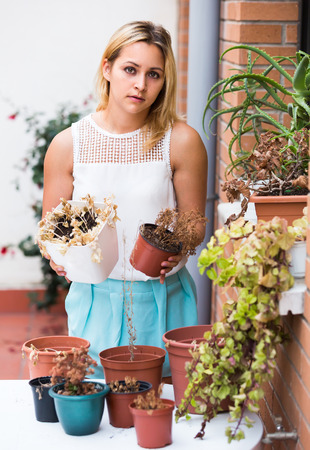 shrunken: Portrait of unhappy girl discovering shrunken plants at terrace Stock Photo