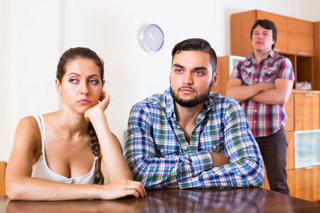 lovers quarrel: Portrait of unhappy attractive girl and two guys at home: problems of love triangle