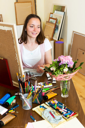 contentedness: Positive young artist paints a picture at home Stock Photo