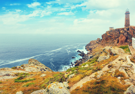 spain: Toned photo with the lighthouse on the rocky coast. Galicia, Spain Stock Photo
