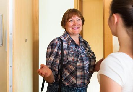 puerta abierta: Dos mujeres caucásicas adultos de pie junto a la puerta