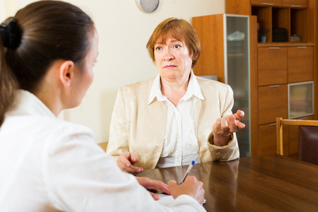 mature people: Adult unhappy women talk seriously about some important things Stock Photo