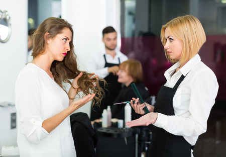negatively: Displeased young attractive girl negatively talking with the hairdresser