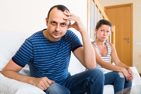 tired: Ordinary american family couple shouting while arguing indoors