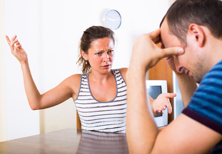 woman shouting: Angry young woman and her tired husband quarreling at home Stock Photo