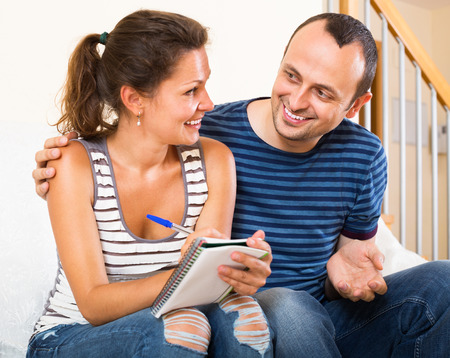 spouses: Happy spouses filling shopping list and smiling at home