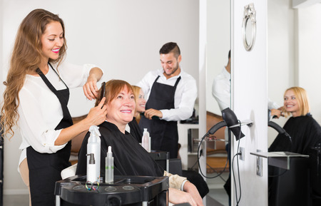 ordinary woman: Mature person haircut at the hair salon with hairstylist and smiling