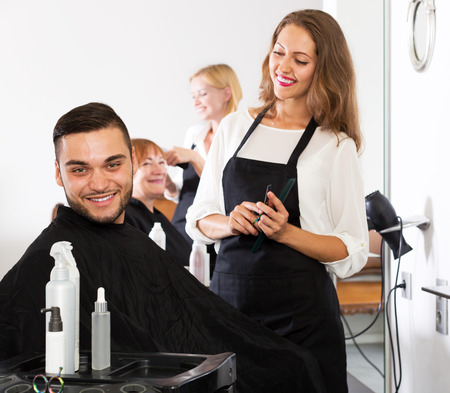 hairdressing salon: Cheerful young guy cuts hair and female barber at the hair salon