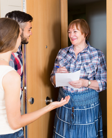 neighbours: Smiling mature female conducting survey among neighbours Stock Photo