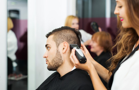 haircutter: Haircutter makes the haircut for man in the hairdressing salon