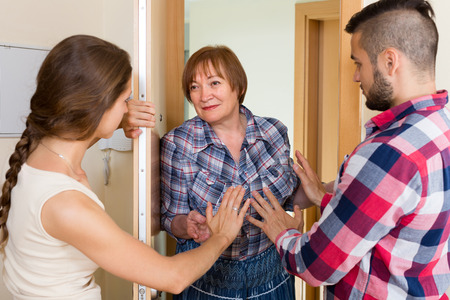 neighbour: Displeased young family arguing with elderly female neighbour in the doorway