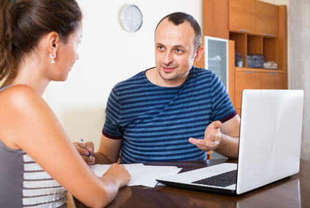 financial planning married: Adult couple sitting at desk with papers and laptop at home