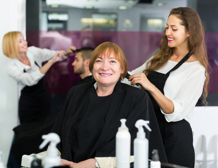 elderly: Elderly woman doing haircut  with girl hairstylist at the hair salon