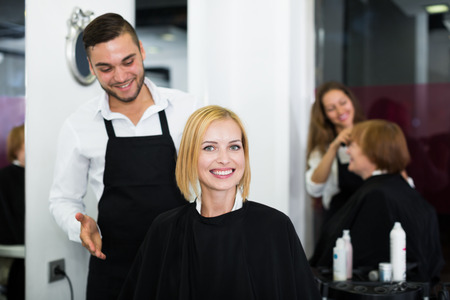 peignoir: Hair stylist working on haircut for young woman. Focus on the woman Stock Photo