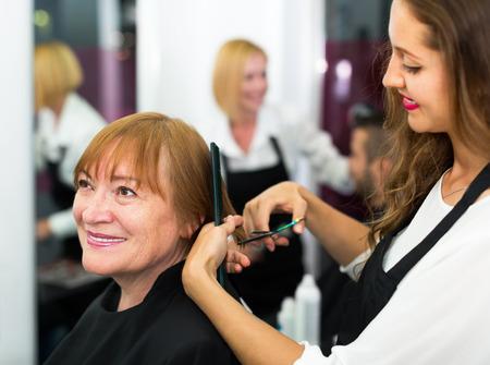 peignoir: Elderly woman doing haircut at barbershop