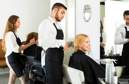 hairtician: Male hairstylist is making a haircut for a happy woman in a barbershop. Focus on client