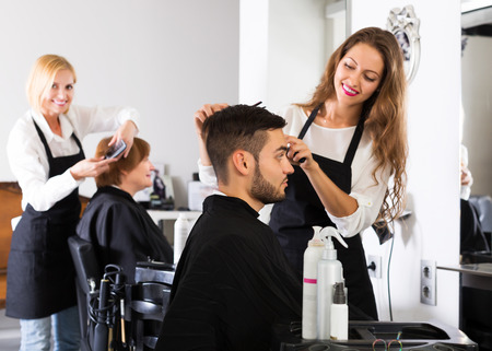 Smiling professional hairdresser doing hairstyle for young men