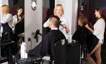 kapster: De kapper maakt het kapsel voor jonge man in de kapperszaak Stockfoto