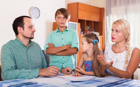 complaints: Parent with two children making customer complaints at office interior. Focus on man