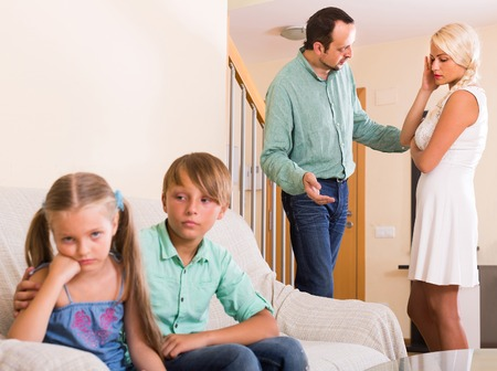 spanish home: Children in silence while spanish parents arguing at home. Focus on adults