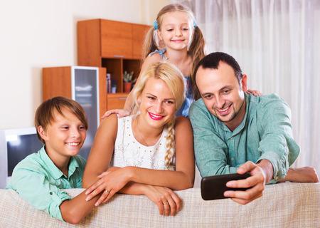 clase media: Retrato de la sonrisa familia de clase media en el interior de una casa. Centrarse en la mujer Foto de archivo