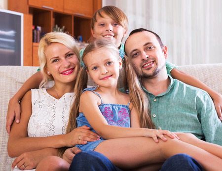 middle class: Portrait of smiling middle class caucasian family at home interior. Focus on girl Stock Photo