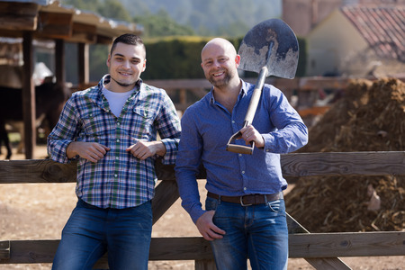 workmen: Two workmen posing with shovels near stables and smiling
