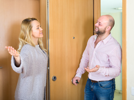 come in: Happy smiling beautiful woman invites her boyfriend to come in in her apartment