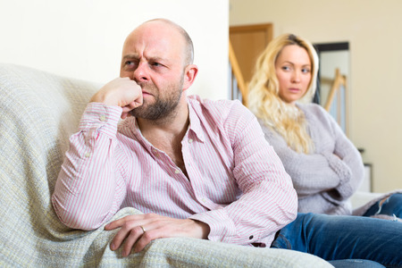 soul mate: Resenting adult man sitting on a couch turned away from his soul mate that is looking at him reproachfully