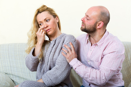 consoling: Sad woman has problem, man consoling her on sofa at home Stock Photo