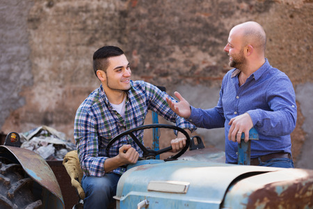sucessful: Two happy male drivers working with tractor and chatting outdoor