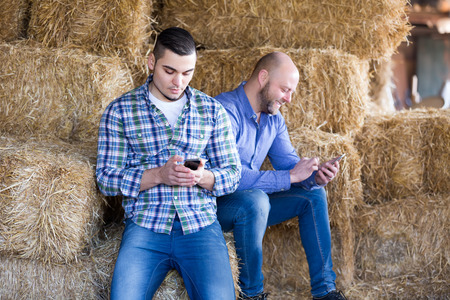 hayloft: Portrait of two male farmers with phones at hayloft. Selective focus Stock Photo