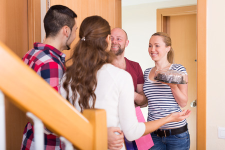 visitors: Happy family couple receiving visitors with gifts in the home