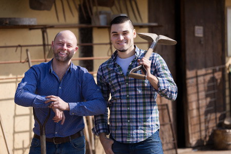 farmyard: Two smiling male farmers standing with spades at farmyard Stock Photo