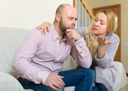 fracas: Woman asking for forgiveness from man after quarrel at home. Focus on guy