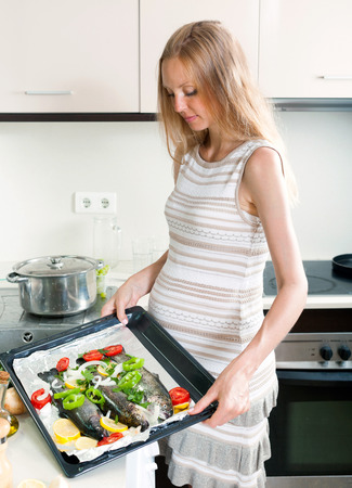 pregnant blonde: Pregnant blonde housewife cooking trout fish in pan at kitchen
