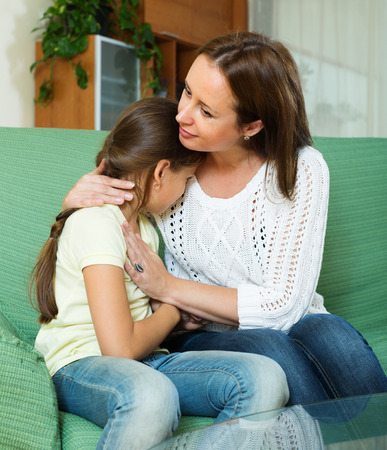 home comforts: Mother comforting crying  daughter at home