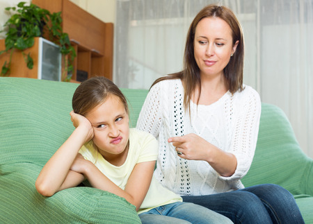 scold: adult woman scolding crying child at their home interior . Focus on girl