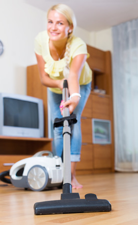 cleanup: Young female using vacuum cleaner during regular clean-up Stock Photo