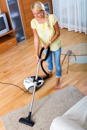 limpieza del hogar: Feliz chica rubia aspiradora en la sala de estar y la sonrisa Foto de archivo