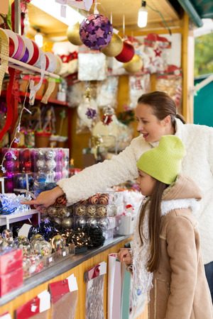 overspending: woman with a young daughter choose holiday decorations on the Christmas market. Focus on girl Stock Photo